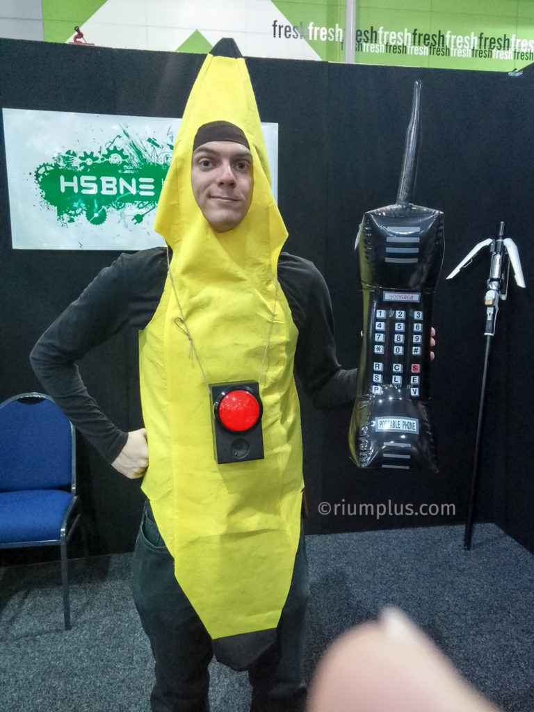 A man wearing a bright yellow banana costume, carrying a giant 75cm long inflatable phone. A black box with a big red button & speaker is dangling around his neck.