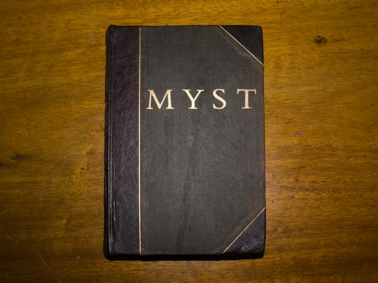 A brown book with black edges and the word MYST embossed on the front in gold