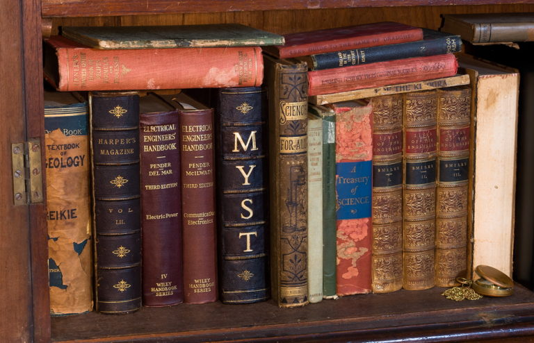 A bookshelf filled with science, engineering & fantasy books with the Myst book in the middle
