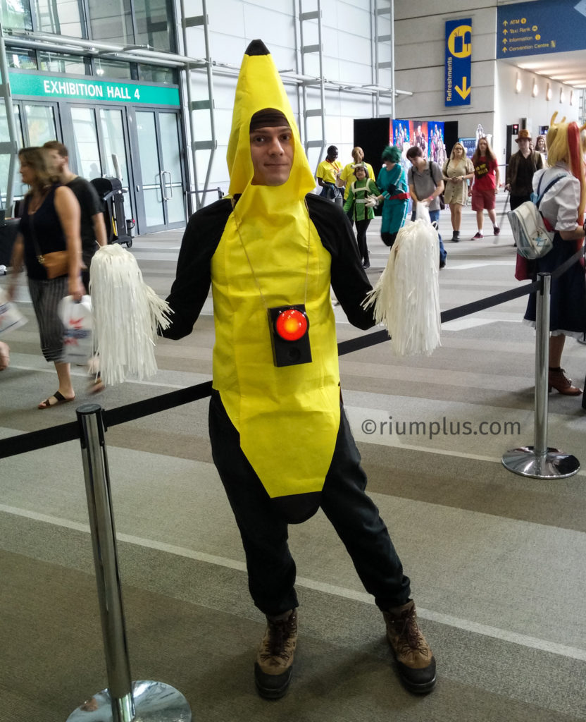 A man wearing a bright yellow banana costume, with white pom-poms in each hand. A black box with a big red button & speaker is dangling around his neck.