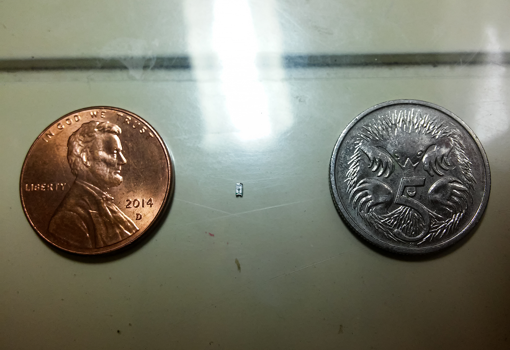 0603 SMD LED compared to a US penny and an Australian 5c coin